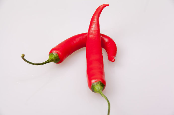 Two red chili peppers on each horizontal format, Raw Chili  Chillis Close-up Food Food And Drink Fresh Freshness Green Chili Pepper Green Color Habanero Healthy Eating Jalapeños Motley No People Pepper Pepper - Vegetable Red Red Bell Pepper Spice Stem Studio Shot Thai Chili Vegetable White Background