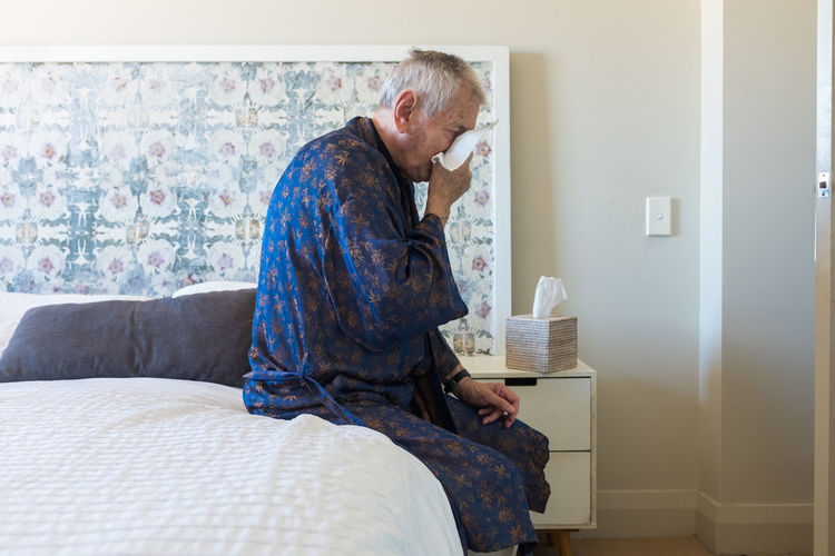 Side view of man sitting on bed at home