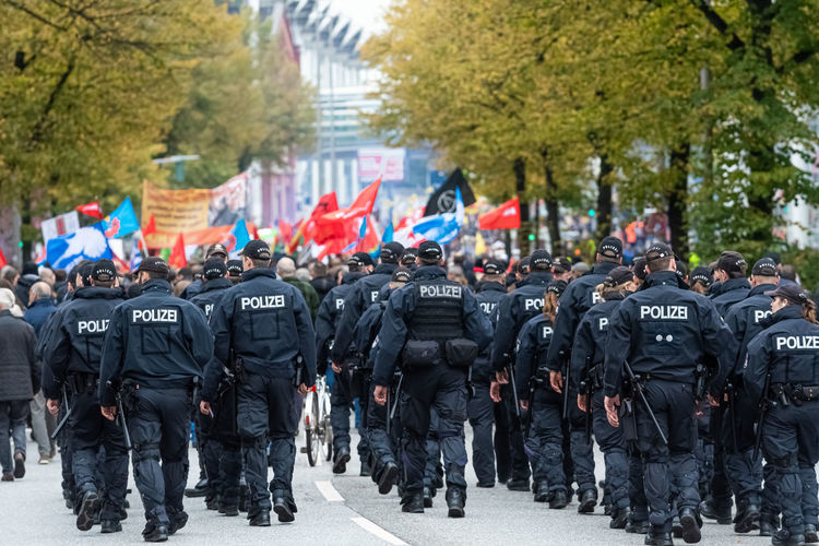 Rear view of police force walking on street