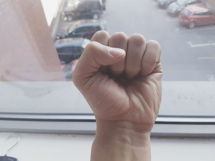 Cropped hand clenching fist by window