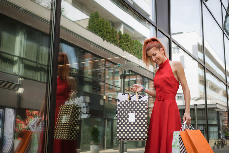 Smiling young woman holding shopping bags while standing by building