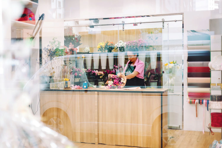 A view through the window of a flower shop and a florist's girl making bouquets