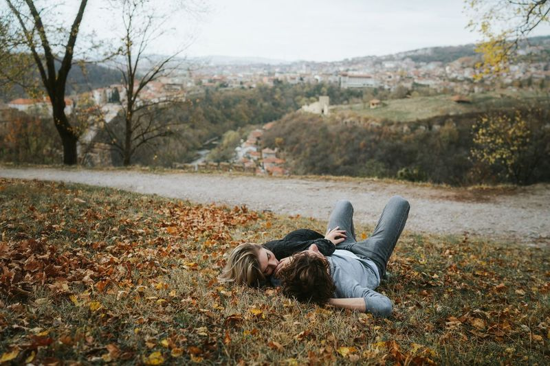 Man lying down on field during autumn