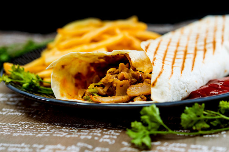 Close-up of fajita and french fries in plate on table
