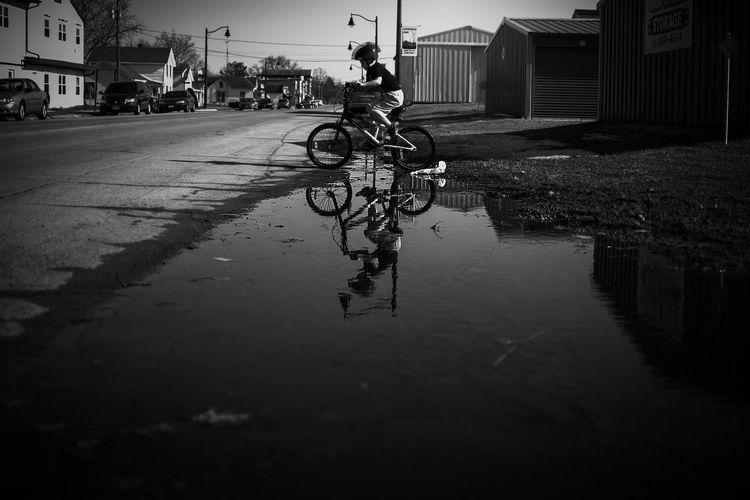 Man riding bicycle on wet street during rainy season