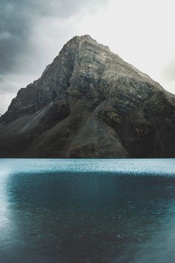 Swimming pool by mountain against sky