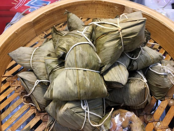 High angle view of leaves covered rice dumplings on wooden container