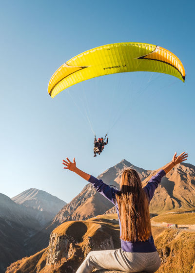 Rear view of person paragliding against sky