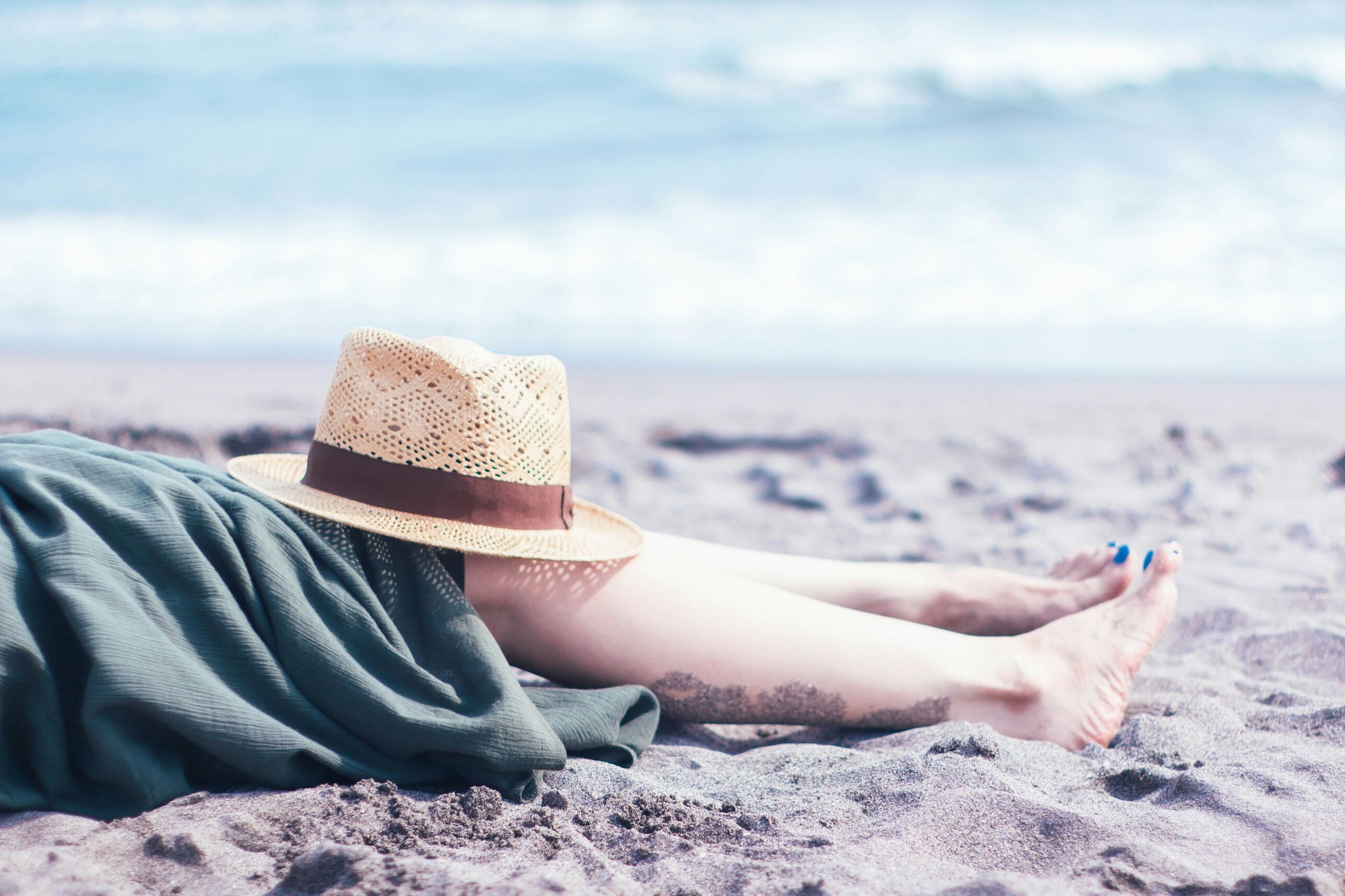 beach, sand, wireless technology, hat, one person, smart phone, real people, portable information device, mobile phone, relaxation, lying down, sea, day, outdoors, women, vacations, nature, leisure activity, lifestyles, water, sky, technology, horizon over water, leisure, sitting, young adult, beauty in nature, low section, young women, close-up, adult, people
