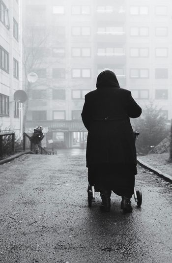 Rear view of a silhouette woman walking in city