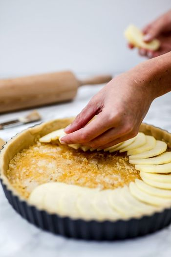 Close-up of person preparing apple pie