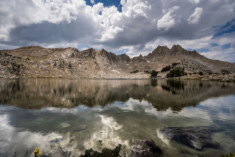 Solitude of afternoon | JMT DAY 9 - CLOUDS LINGERING OVER CHIEF LAKE Clouds lingering over Chief Lake Before reaching Silver Pass, I made a stop at Chief Lake, one of the lakes below the pass. Although it was not a small lake, not a single soul was around enjoying the view. It seemed like one of those lakes no one stopped to enjoy, just like Hitchcock Lakes below Trail Crest. It only meant that I kept it all to myself and enjoyed solitude of afternoon. What a beautiful lake. At first the winds that constantly blew didn't let me capture the reflection of the ridge surrounding the lake below the pass. So, I considered doing long exposure. But, I had to keep up with my JMT buddy Henry. So, I decided to go against it. Very brief moments of calmness came and went, and I saw the clouds forming super fast over the ridge. It was quite exhilarating to watch how quickly these clouds form and dissipate over and over. Such a beautiful and awe-inspiring imagery can turn the whole place upside down in a matter of minutes. I really hoped that they wouldn't turn into rain clouds till I at least reached the pass. And they did didn't. I wished I had had more time at the lake. But I knew I had to go. I reluctantly packed away my gear and put on my heavy backpack. Chief Lake, Sierra National Forest, CA Water Sky Cloud - Sky Mountain Scenics - Nature Lake Reflection Beauty In Nature Tranquil Scene Tranquility Nature No People Mountain Range Idyllic Non-urban Scene Outdoors Chief Lake, Sierra Nevada Nature Landscape JMT Adventure