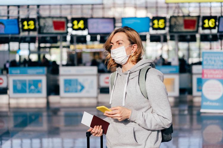 Woman wearing mask holding mobile phone walking outdoors