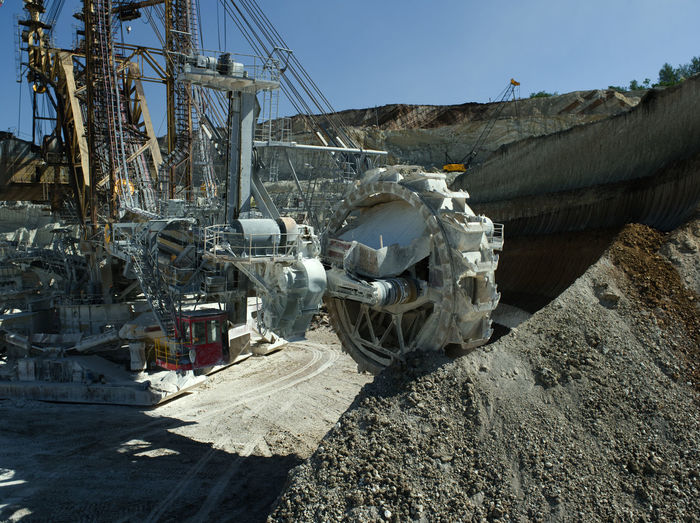 Bucket-wheel excavator at open-pit mine against clear sky