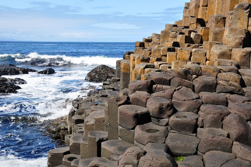 Rock Formations At Giant Causeway By Sea Against Sky