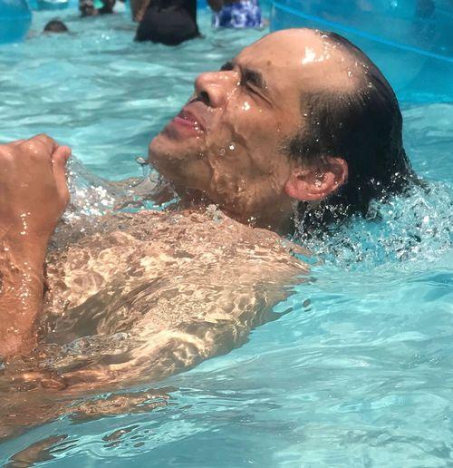 Side view of shirtless man enjoying in swimming pool