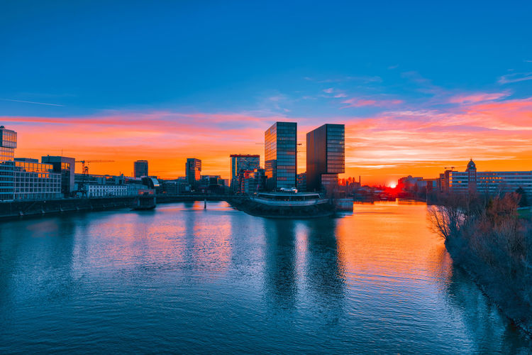 Duesseldorf, GERMANY - February 25, 2019: The modern buildings of the new media harbor gloom in the sinking sun light Düsseldorf Media Harbor Medienhafen Blue Hour High Resolution Architecture Building Exterior Built Structure Sky City Water Sunset Waterfront Building Office Building Exterior Cityscape Skyscraper Urban Skyline No People Cloud - Sky Orange Color Nature River Landscape Tall - High Modern Outdoors Financial District