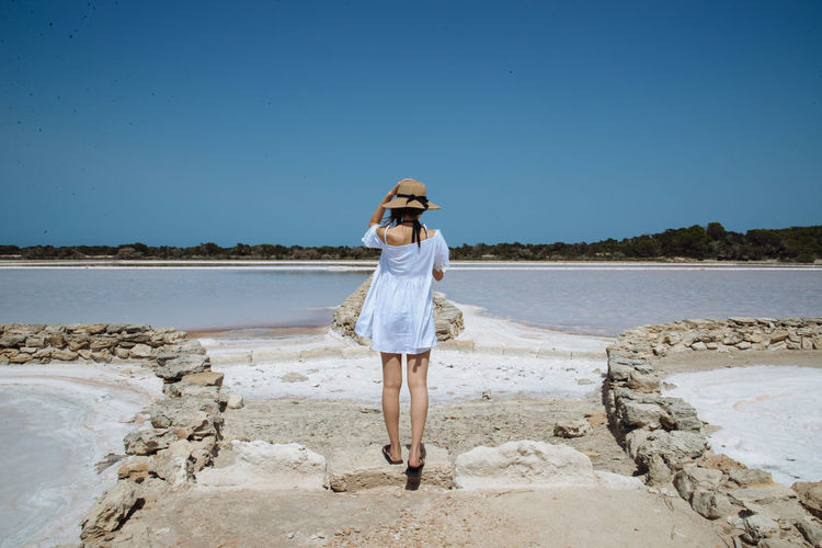 Beauty In Nature Blue Casual Clothing Clear Sky Copy Space Day Full Length Hat In Front Of Leisure Activity Lifestyles Nature Paving Stone Person Scenics SPAIN Standing Sunset Tranquil Scene Tranquility Vacations Water Weekend Activities Young Adult Young Woman