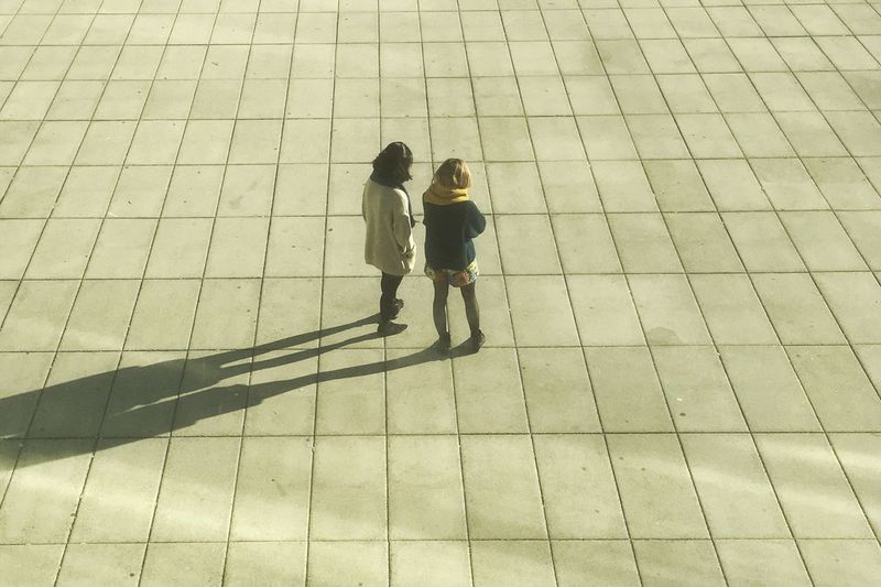 High angle view of friends walking on tiled floor