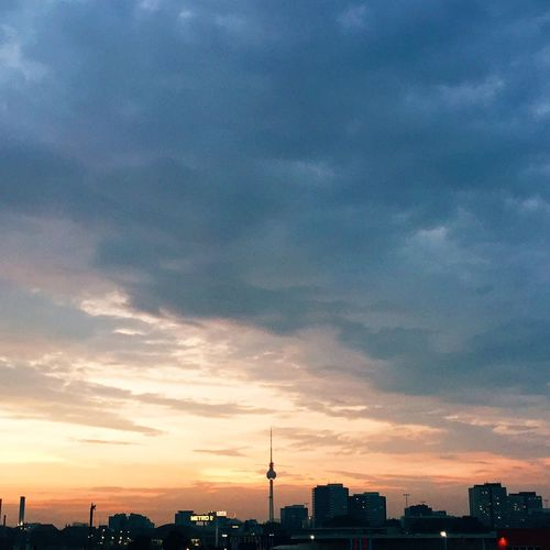 Cityscape against cloudy sky at sunset