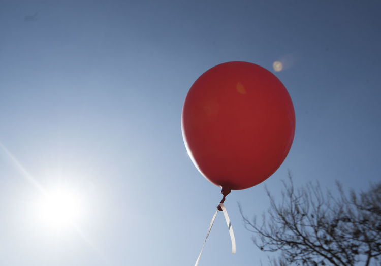 Low angle view of red balloons against sky