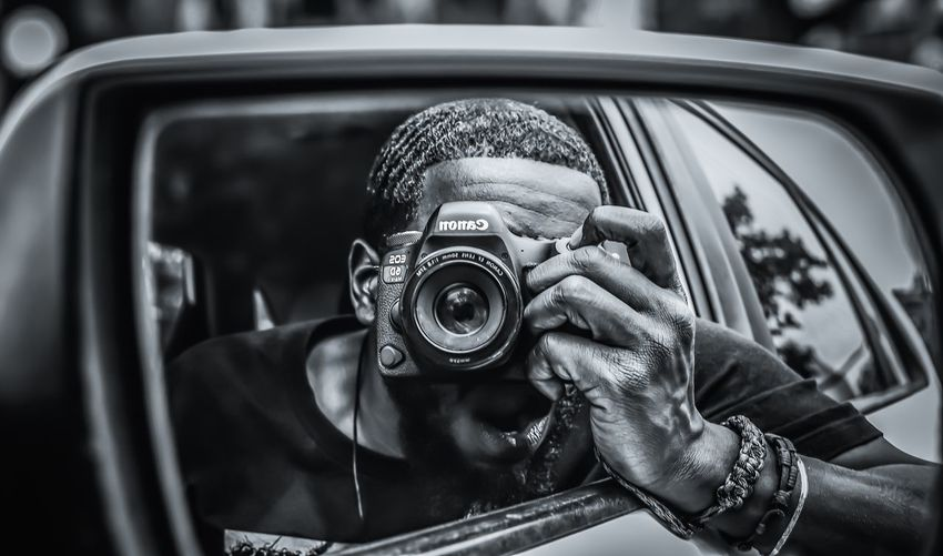 Portrait of man photographing car