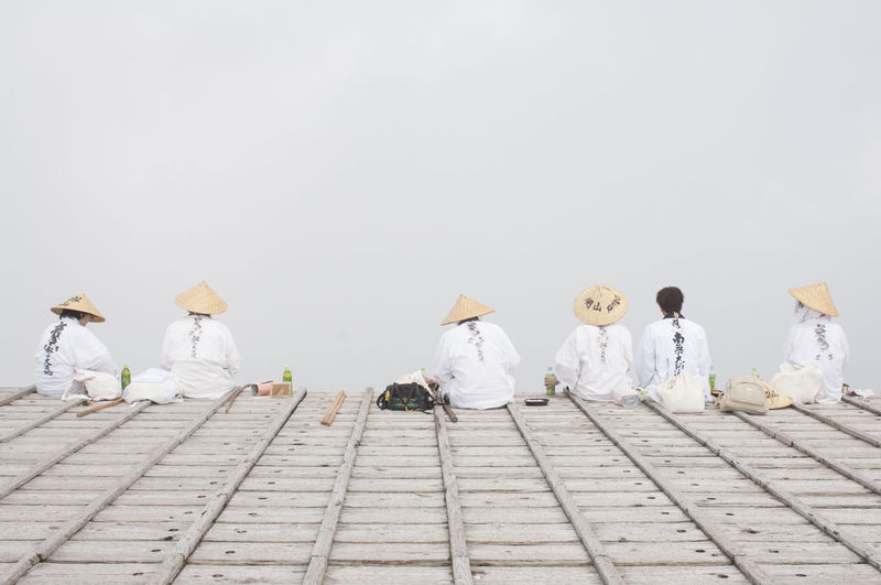 Rear View Of People Wearing Asian Style Conical Hats Sitting In Row Against Sky