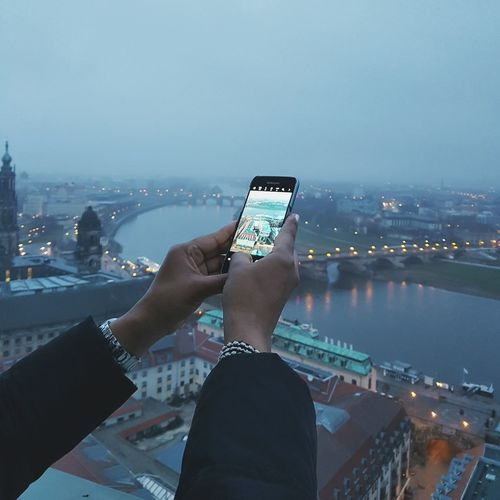 A view Wireless Technology Communication Mobile Phone Smart Phone Portable Information Device City Urban Skyline Samsung Human Body Part Human Hand Holding Mobile Conversations Female Hand Greeting Card  Full Frame Fingers Dawn Citylights Skyline Dresden River Flying High Taking Photos Technology Stories From The City