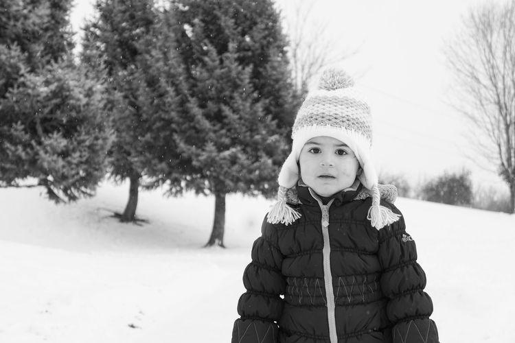 Portrait Of Cute Girl Wearing Warm Clothing Standing On Snowy Field