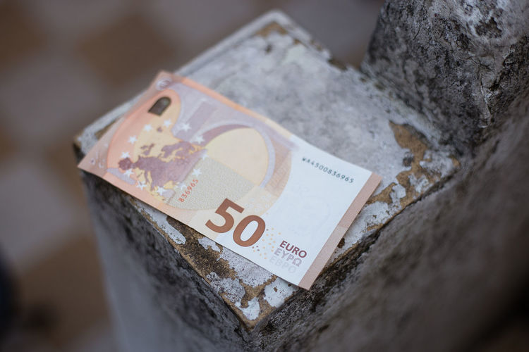 High angle view of paper currency on concrete