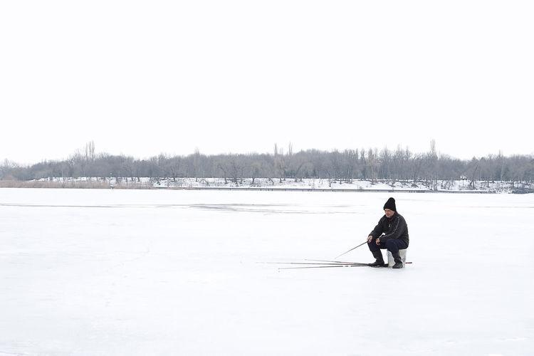 Full length of man fishing on frozen lake against clear sky