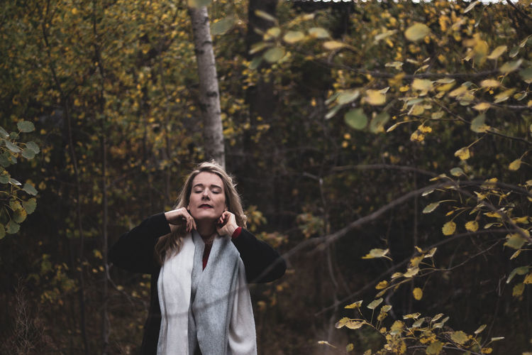 Mid adult woman with closed eyes standing against trees in forest