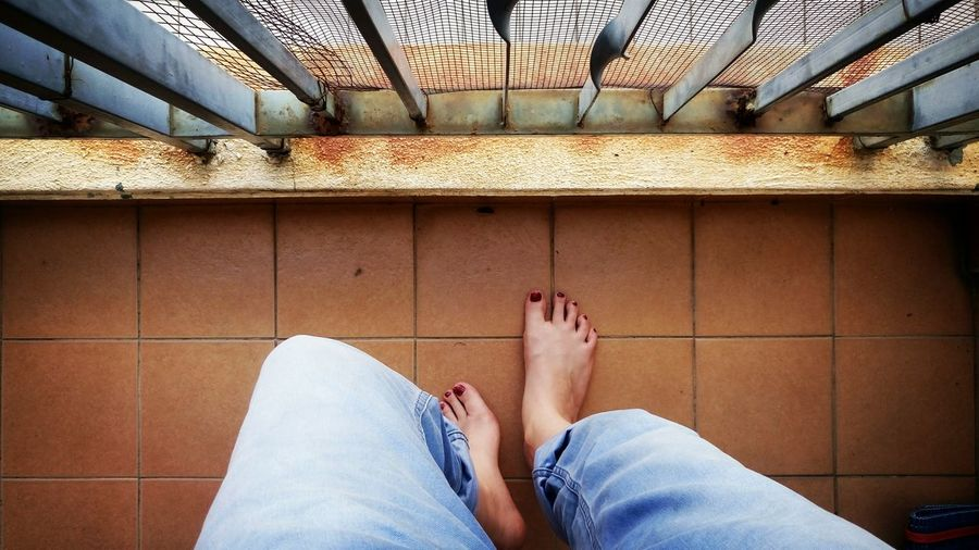 Low section of feet relaxing on a balcony