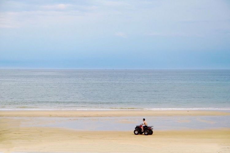 Man riding quadbike at beach against sky during sunset