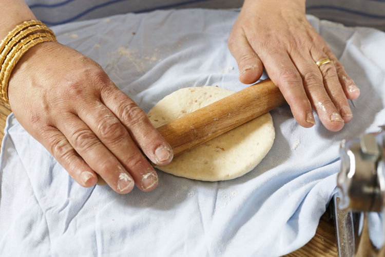 Cropped image of woman preparing dough at home