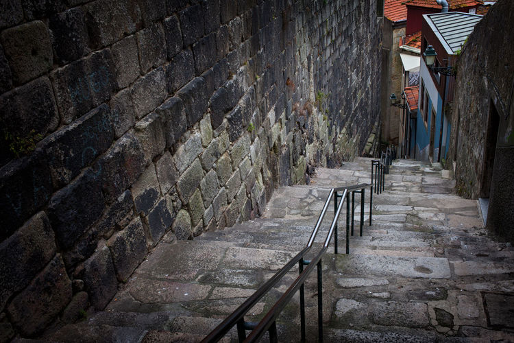 Stairs along medieval stone wall in the Old Town of Porto in Portugal Dark Old Town Oporto Porto Portugal Railing Stairs Stairway Wall Architecture Building Building Exterior Built Structure Down Europe Grunge Historic Medieval No People Old Old City Staircase stairways Steps Stone