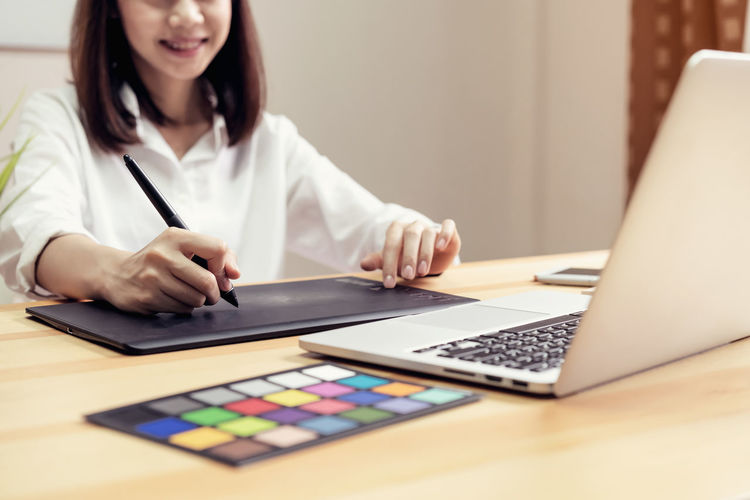 Midsection of businesswoman with laptop and color swatch on table