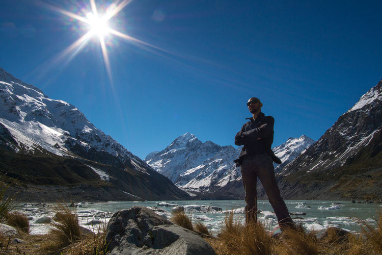 Low angle view of man standing by river against snowcapped mountain sky