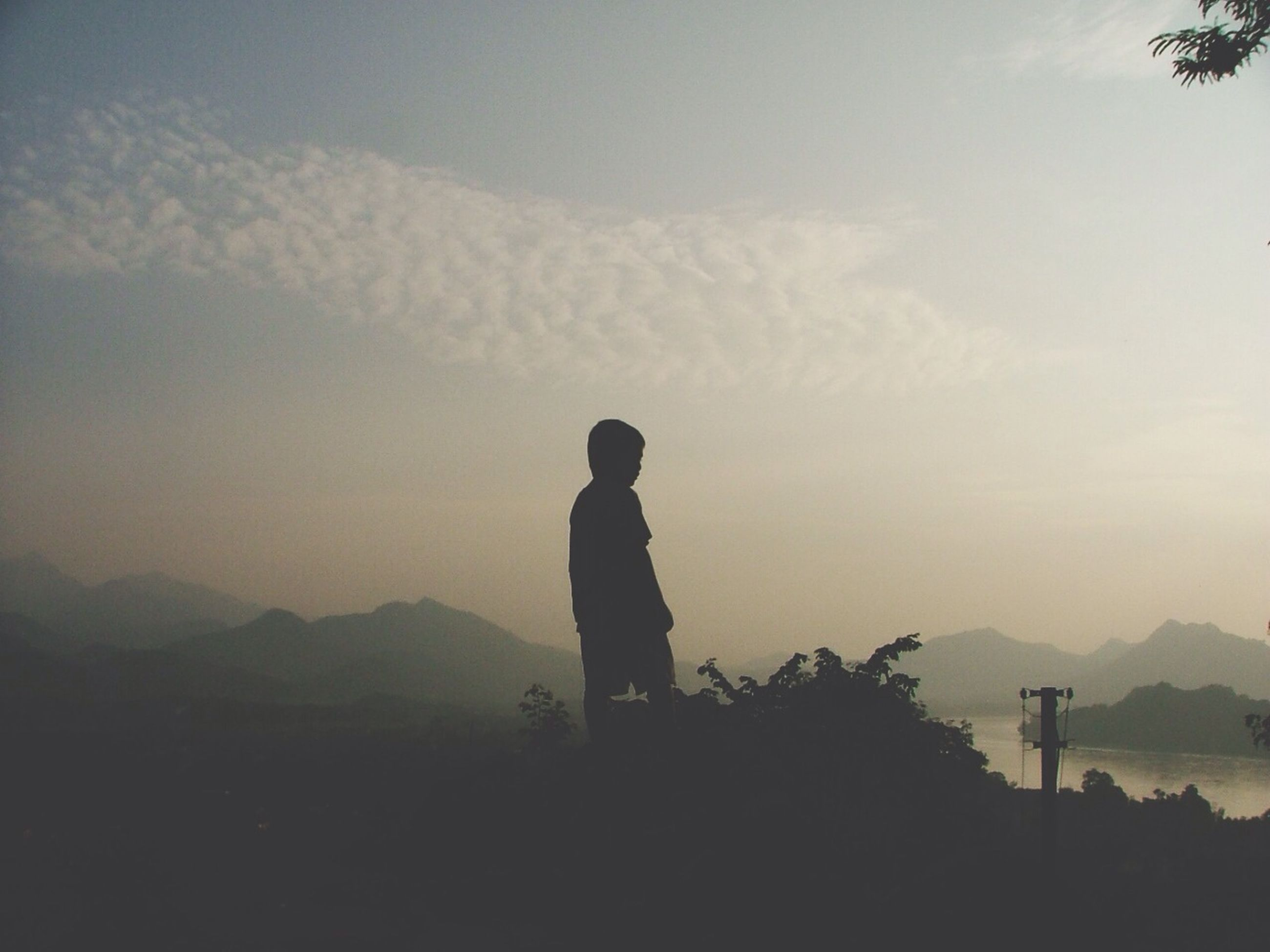 silhouette, lifestyles, leisure activity, standing, sky, rear view, tranquility, tranquil scene, men, mountain, scenics, beauty in nature, full length, nature, landscape, getting away from it all, person, cloud - sky
