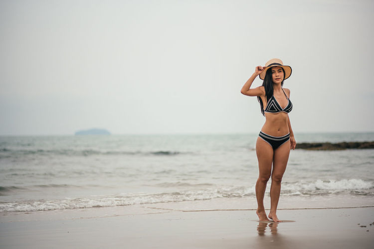 Beach Sea Land Clothing One Person Water Standing Young Adult Young Women Swimwear Bikini Full Length Sky Hat Horizon Over Water Lifestyles Leisure Activity Front View Fashion Beautiful Woman Sun Hat