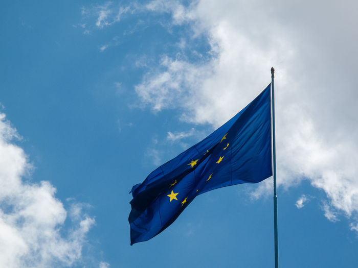 Low angle view of european union flag against cloudy sky