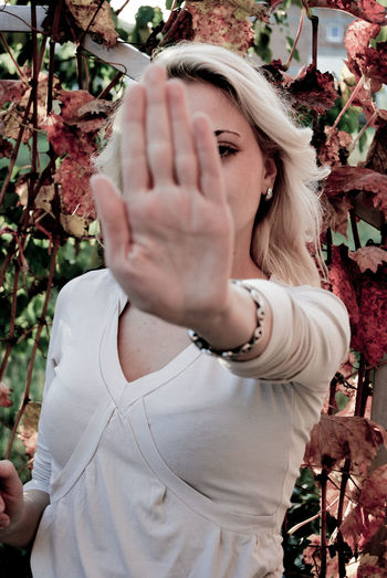 Woman gesturing stop while standing against plants