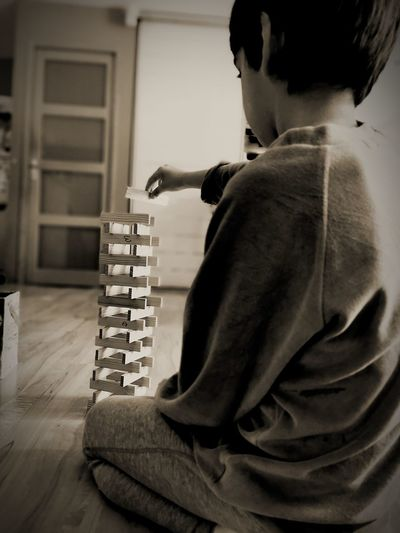 Side view of boy playing block removal game at home