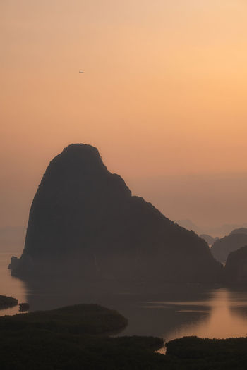 Silhouette rocks by sea against orange sky