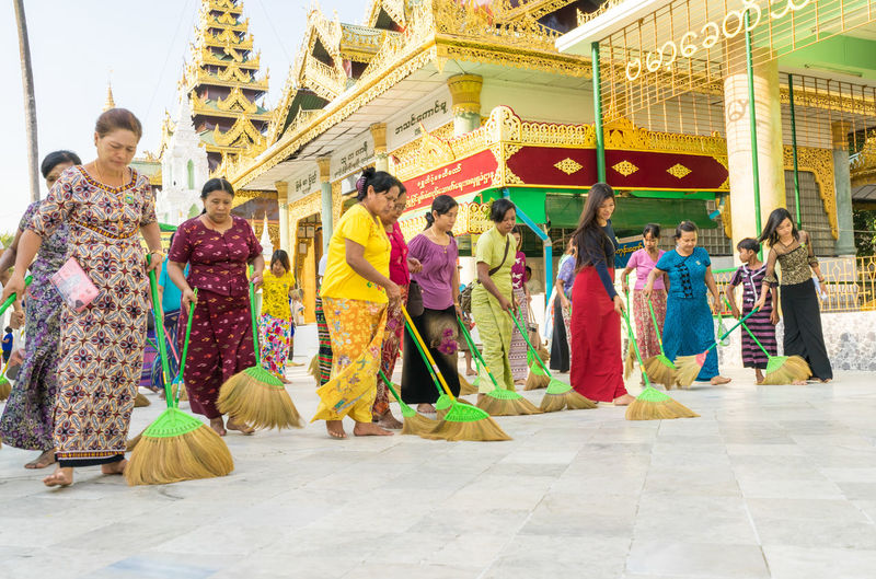 Buddhism pilgrimage participate in a ceremony with brooms sweeping at the Shwedagon Pagoda. Buddhism Pilgrimage Shwedagon Pagoda Sweeping The Floor Yangon, Myanmar Adult Architecture Built Structure Burma Burma People Burmese Group Group Of People Group Of Peoples Lifestyles Men Myanmar People Pilgrimage Real People Religion Religion And Beliefs Religious  Shwedagonpagoda Sweeping Women