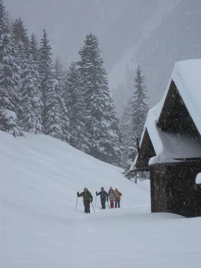 Hikers walking on snow against sky