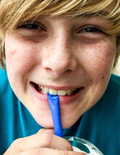 Portrait Of Cheerful Boy Drinking From Straw