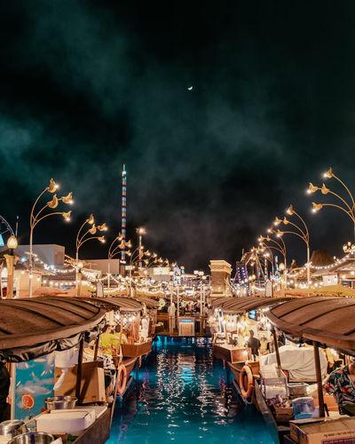 Boats moored at harbor against sky at night