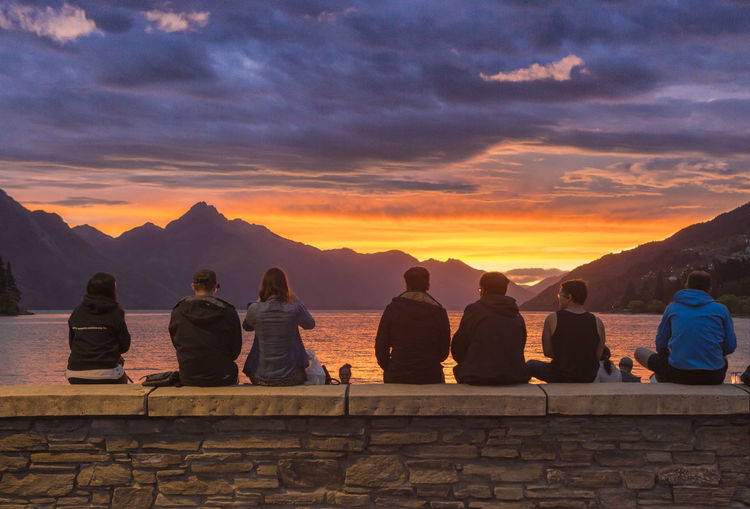 Rear View Of People Sitting On Retaining Wall Against Sky During Sunset