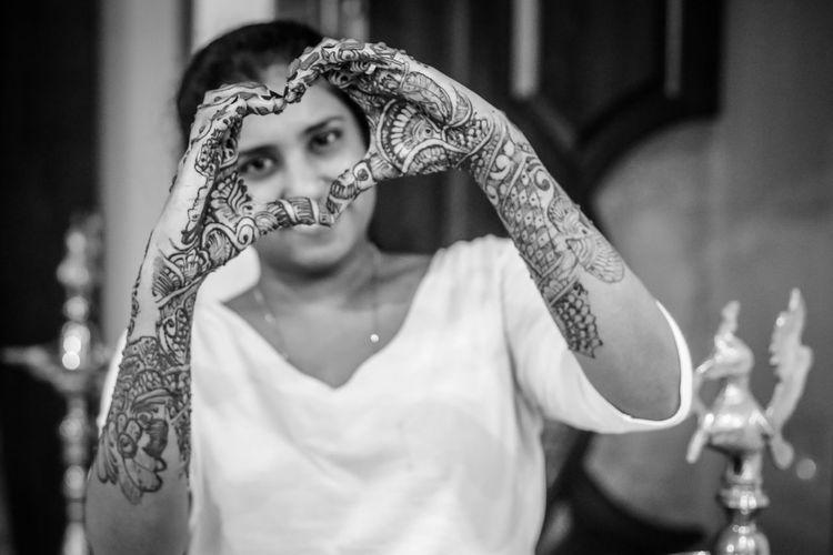 Woman with henna tattoo making heart shape
